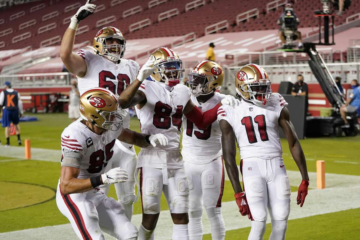 Teammates celebrate with Brandon Aiyuk, far right, of the San Francisco 49ers after Aiyuk scored a touchdown against the Los Angeles Rams during the second quarter at Levi's Stadium on Oct. 18, 2020, in Santa Clara, Calif.