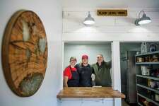 From left, Abbi Brady, Jack Brady and Mike Brady pose for a photo inside Jack's Hometown Pizza as it reopens Saturday for the first time since the building was damaged during the May 19 dam failures and flooding. For more photos, visit www.ourmidland.com. (Katy Kildee/kkildee@mdn.net)