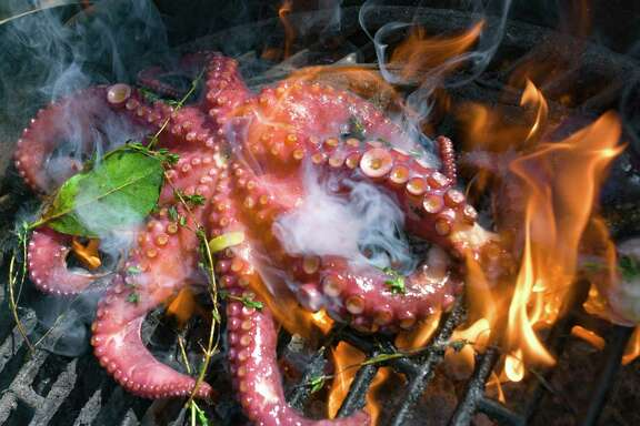 An octopus sizzles over the hot coals of the charcoal grill.