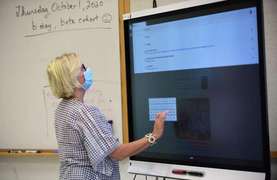 A teacher sets up her technology in the classroom at Brien McMahon High School in Norwalk Photo: Erik Trautmann / Hearst Connecticut Media / Norwalk Hour