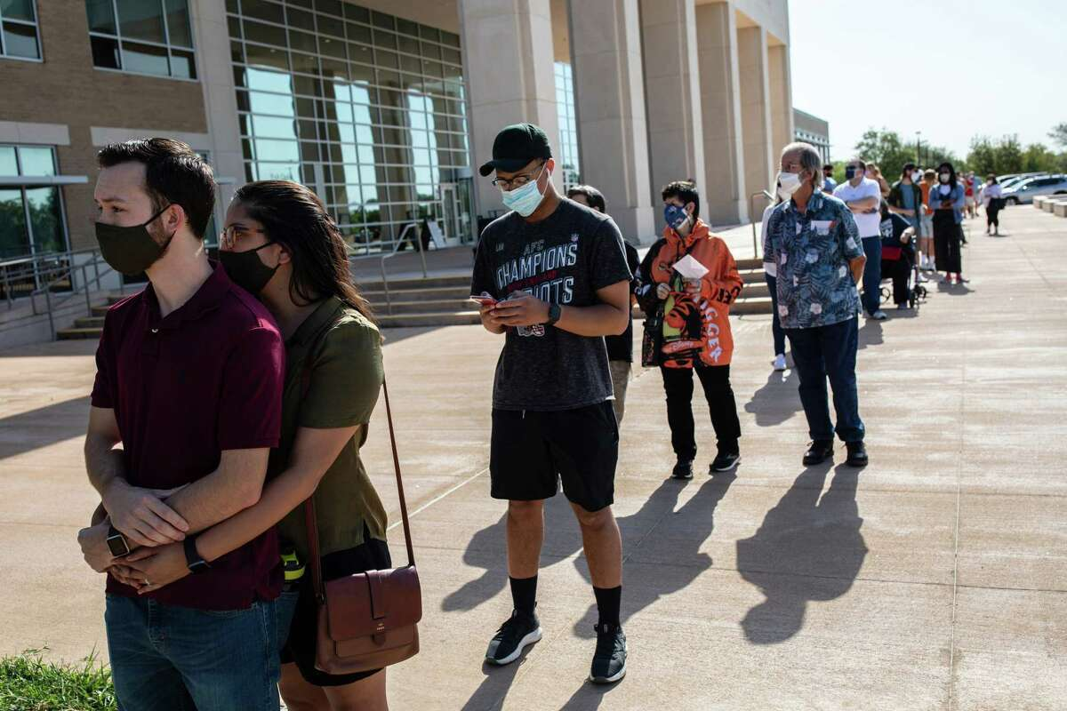 People line up to cast their ballots at the Hays County Government Center polling place in San Marcos, Texas, Oct. 13, 2020, the first day of early voting.