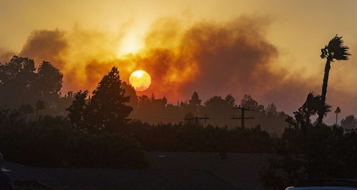 In this view from Newport Boulevard in North Tustin, the morning sun rises through the smoke of fire in the canyons east of North Tustin on Monday, Oct. 26, 2020. F