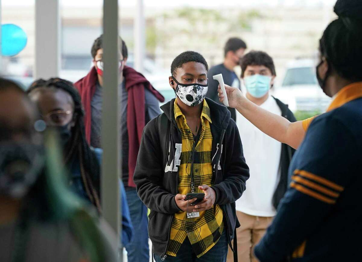 A student has his temperature taken before entering Booker T. Washington High School, 4204 Yale St., on Monday, Oct. 19, 2020 in Houston. Monday was the first day of in-person classes in Houston ISD.