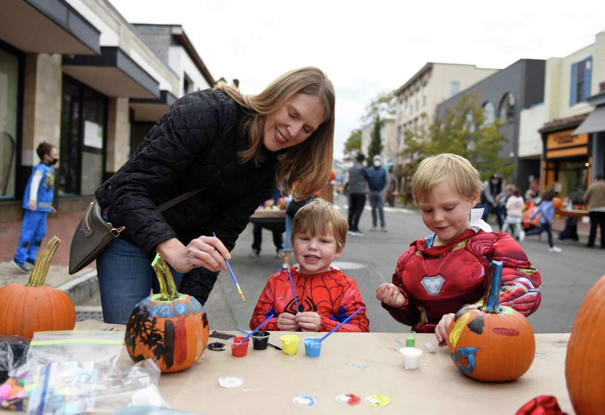 Westport's Lisa Akerson and her children Matthew, 3, and Andrew, 5, paint pumpkins at the Westport Downtown Merchants Association Halloween Family Pumpkinfest in Westport, Conn. Sunday, Oct. 25, 2020. 150 families dressed in Halloween costumes participated in the socially-distant pumpkin painting event, presented by the Westport Parks & Recreation and Westport Police Athletic League in partnership with the WDMA.