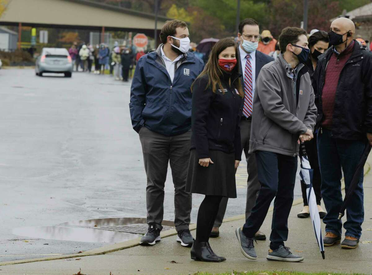 Congresswoman Elise Stefanik, foreground left, and her husband, Matt Manda, foreground right, wait in line to cast their ballots in early voting at Gavin Park on Monday, Oct. 26, 2020, in Saratoga Springs, N.Y. (Paul Buckowski/Times Union)