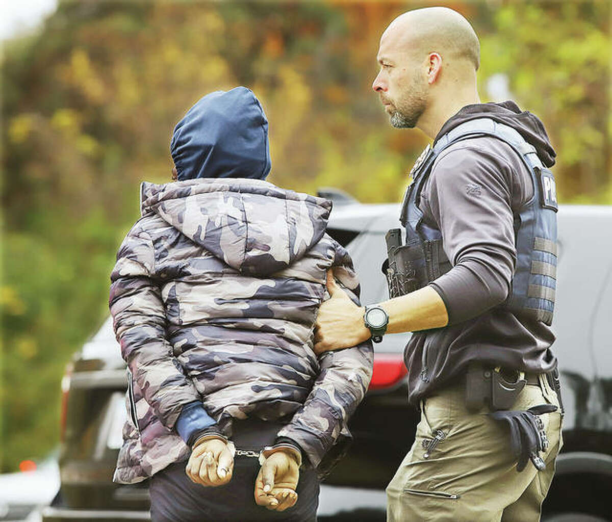 A Wood River Police officer escorts one of four subjects taken into custody to a waiting police car on the highway. Police also had a white Hyundai towed to their station for processing.