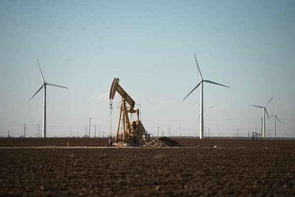 An oil pump jack and wind turbines near Stanton, Texas, on Feb. 21, 2019.