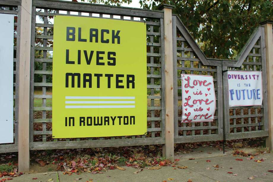 """Rowayton residents again raised a """"Black Lives Matter"""" banner on a community fence Thursday morning, nearly three months after Sixth Taxing District commissioners demanded it be removed. Days later, a """"Back the Blue"""" banner appeared feet away. Photo: /"""