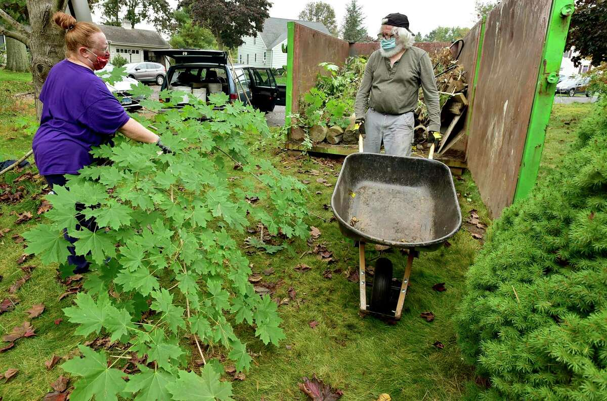 Kelly Miller, left, and Allan (CQ) Wilcox, both of Milford, volunteer with the Milford Land Conservation Trust to cleanup a newly acquired 1.12 acre property with other land trust members at the end of Anchorage Drive Saturday in Milford.
