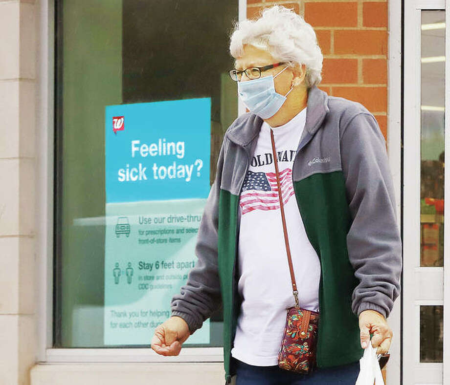 A woman exits the North Alton Walgreens store Monday after shopping with her mask on. Many people have been wearing their masks but many more are not. Starting Wednesday the state will again impose tighter restrictions due to a rise in positive case numbers in the Metro East. Dining and drinking indoors will be prohibited at restaurants and bars starting Wednesday, and gatherings will be limited to 25 people.