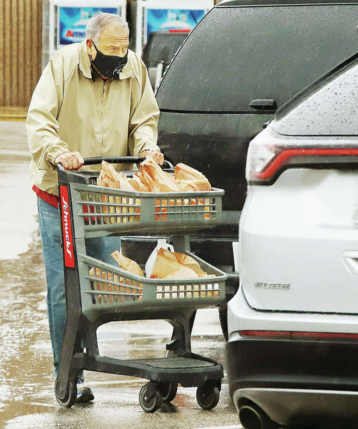 A man, properly wearing his face mask, heads to his car Monday with a cart full of groceries from the Schnucks store in Godfrey. It probably wasn't a bad idea to get groceries since the state will again ban service at indoor restaurants and bars in Madison County starting Wednesday.