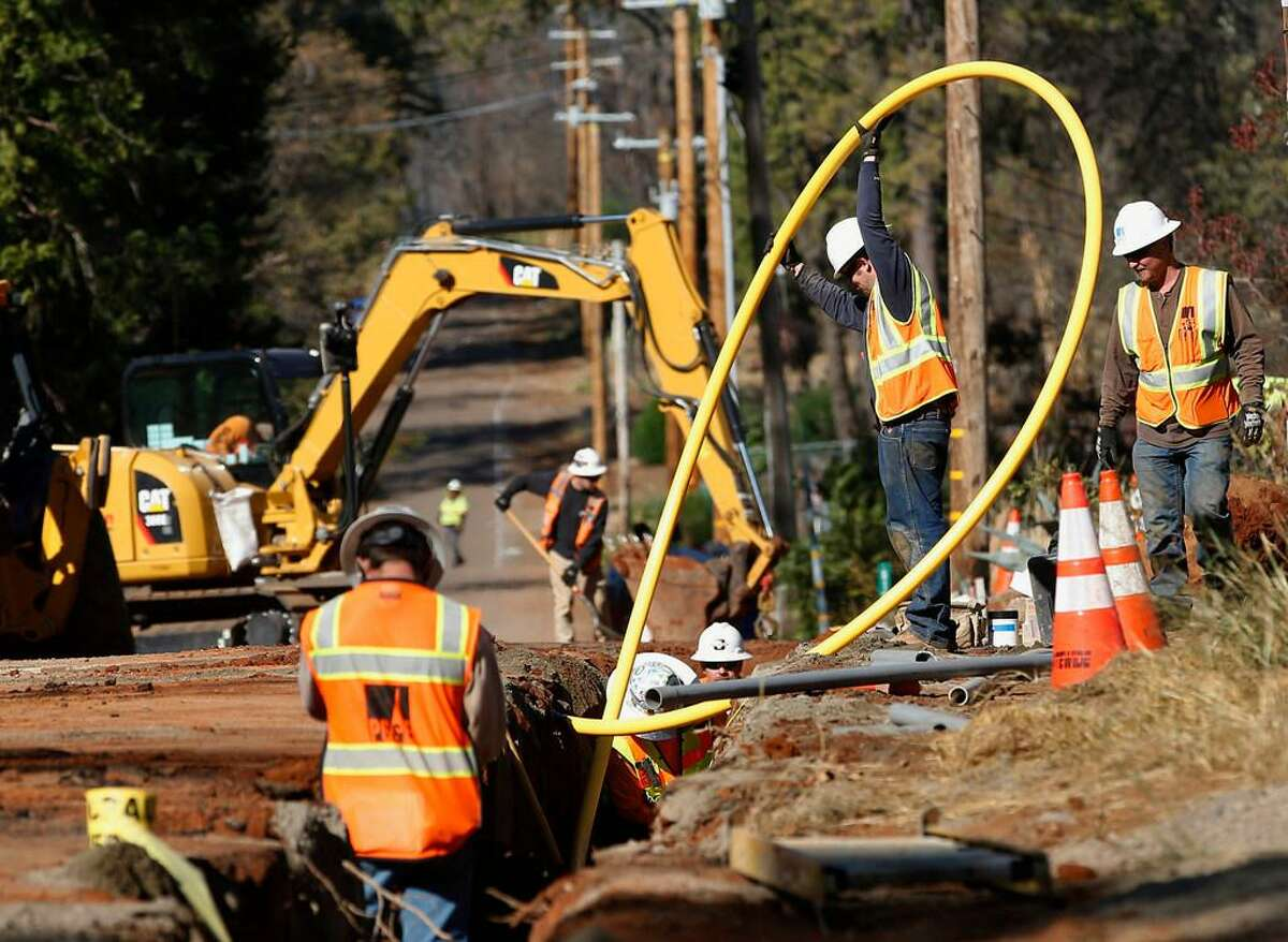 In this Oct. 18, 2019, file photo, Pacific Gas and Electric Company, workers bury utility lines in Paradise, Calif. A new technology being tested by California utilities, such as Pacific Gas & Electric Co. and Southern California Edison, is aimed at diagnosing problems before they could cause power outages or spark wildfires.