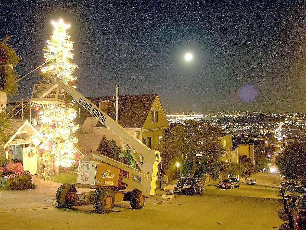 Tom Taylor puts ornaments on his tree next to his house on 21st Street with a cherry picker in 2003.