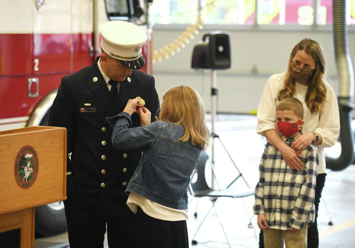 Eric Maziarz receives his pin from his daughter, Caroline, as he is promoted to Deputy Fire Chief at the Public Safety Complex in Greenwich, Conn. Monday, Oct. 26, 2020.