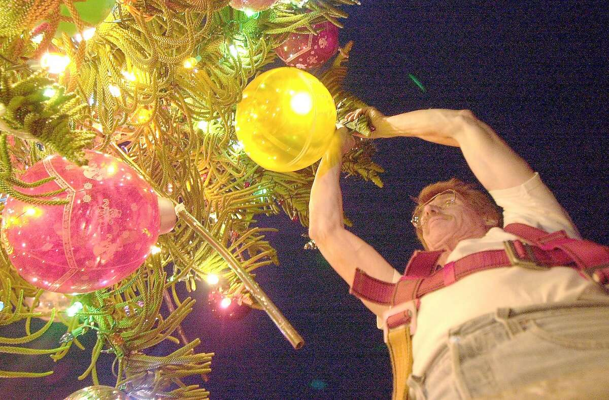 Tom Taylor puts ornaments on his tree next to his house on 21st Street.