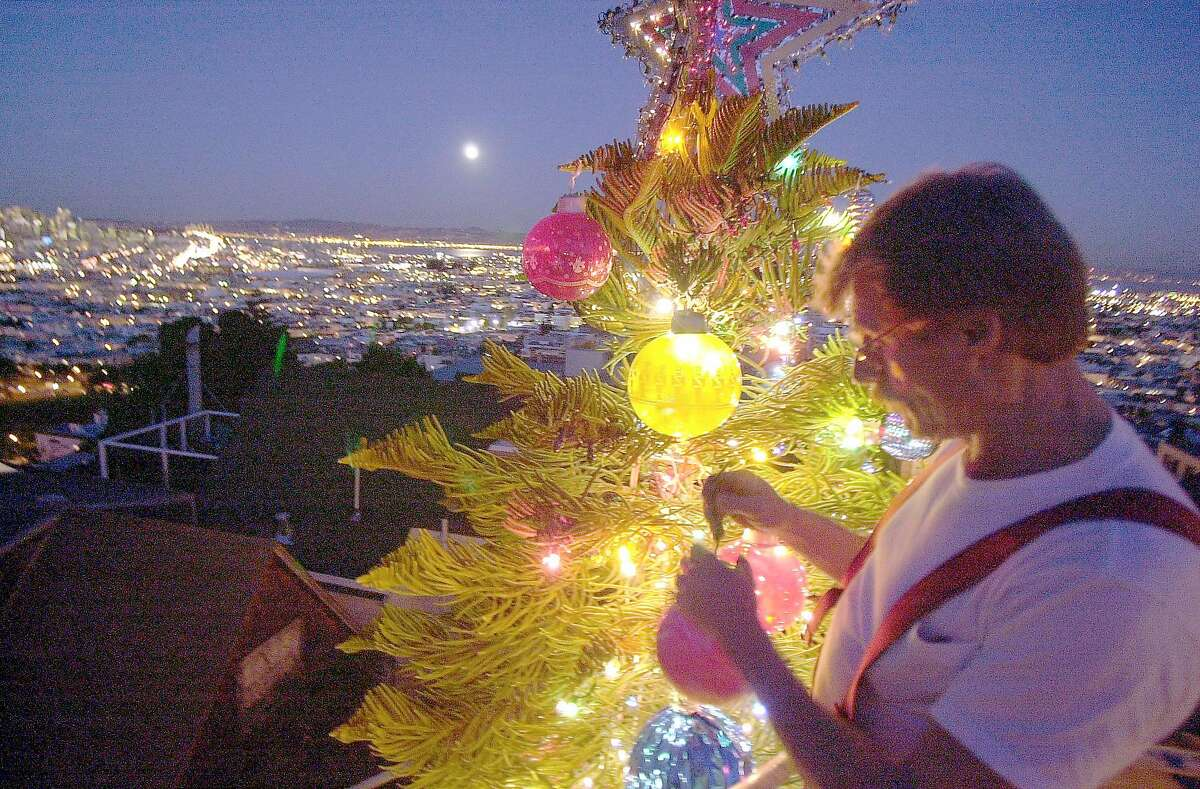 Tom Taylor puts ornaments on his tree next to his house on 21st Street in 2003.
