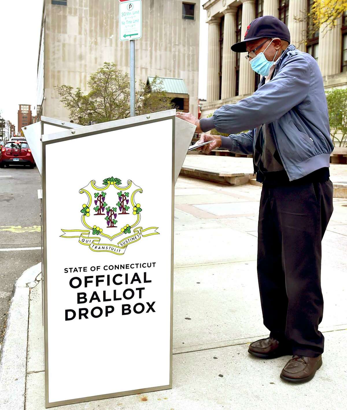Ollie Lawrence drops his ballot into the State of Connecticut Official Ballot Drop Box in front of the Hall of Records on Orange Street in New Haven.