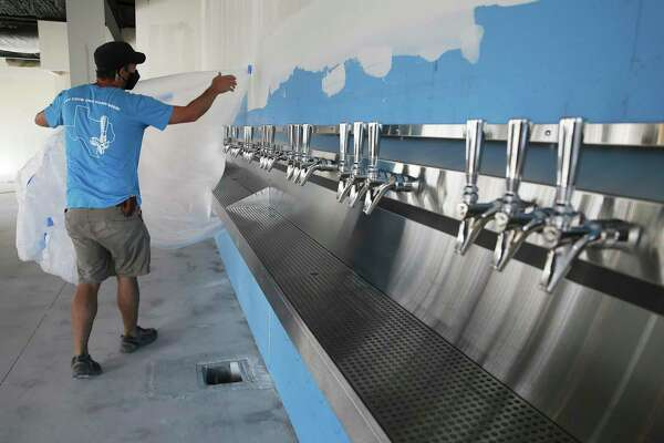 Meredith reveals the 30 self-serving beer taps while crews are working to finish construction of his restaurant and bar.