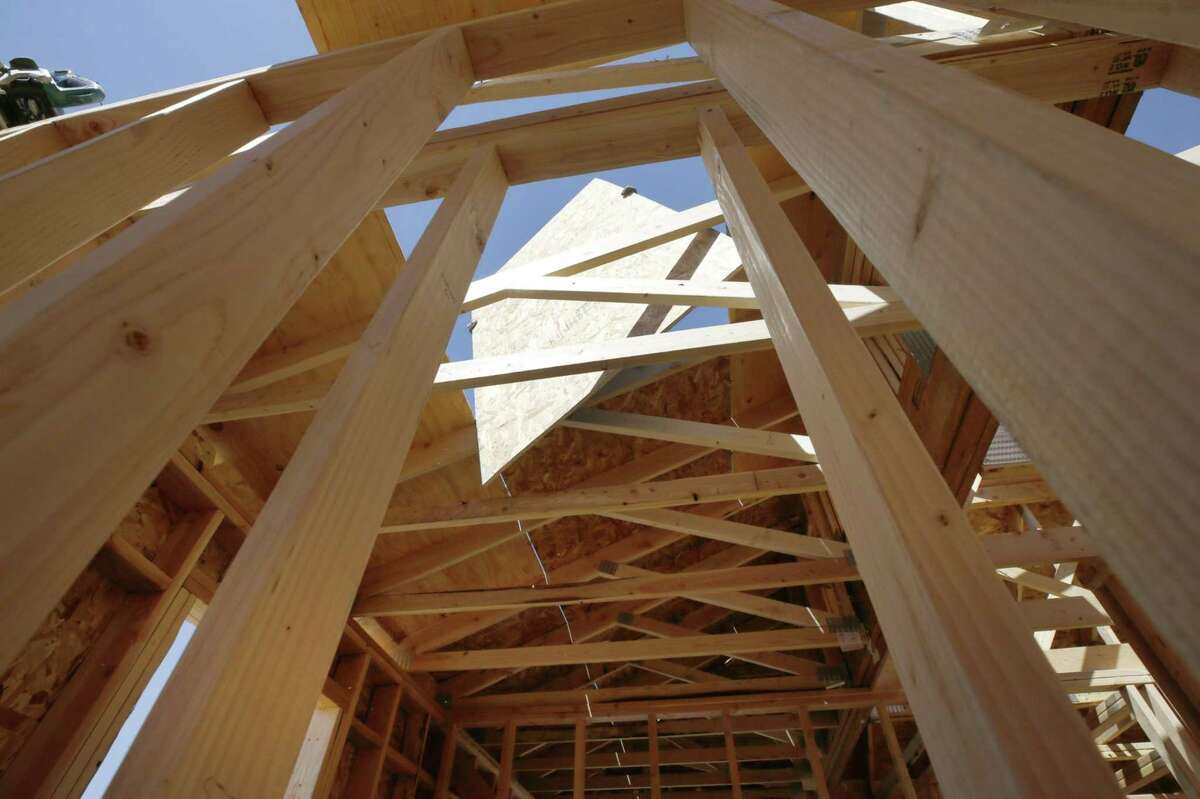 A contractor lifts a sheet of plywood while framing the roof of a home under construction in Park City, Utah.