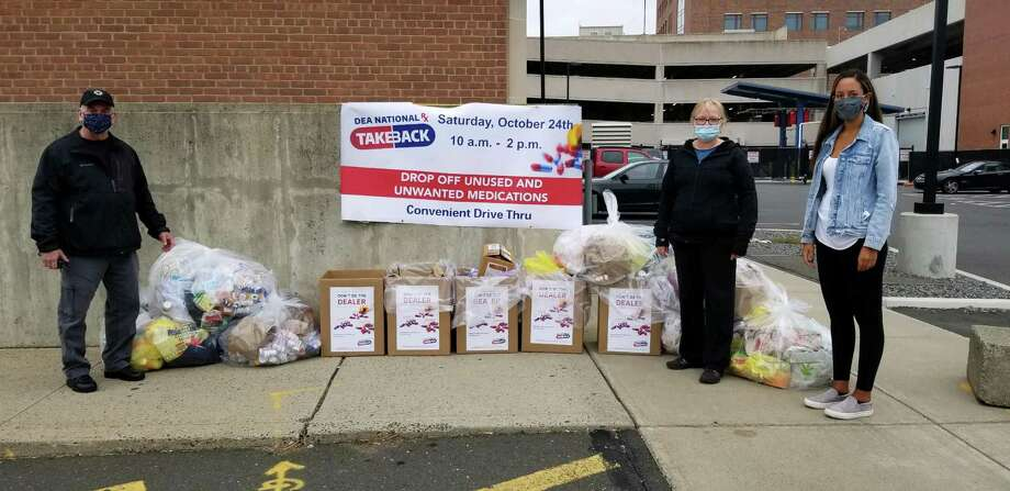 Capt. Richard Conklin (left) standing across from Ingrid Gillespie, director of prevention at Liberation Programs Inc., and (far right) Daniella Arias, program manager at The Hub, the Behavioral Health Action Organization for Southwestern Connecticut. The group collected a record 699 pounds of unwanted superscription drugs. Photo: Stamford Police Department / Contributed