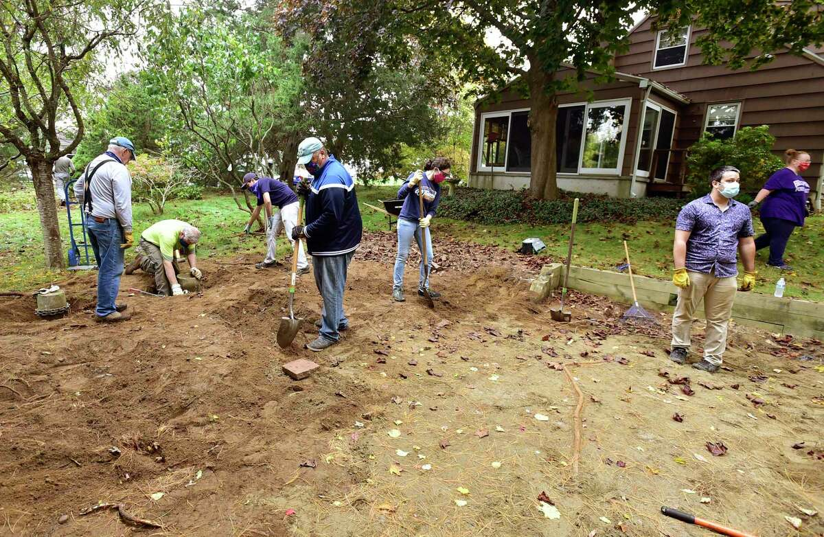 Volunteers with the Milford Land Conservation Trust cleanup a newly acquired 1.12 acre property at the end of Anchorage Drive Saturday.