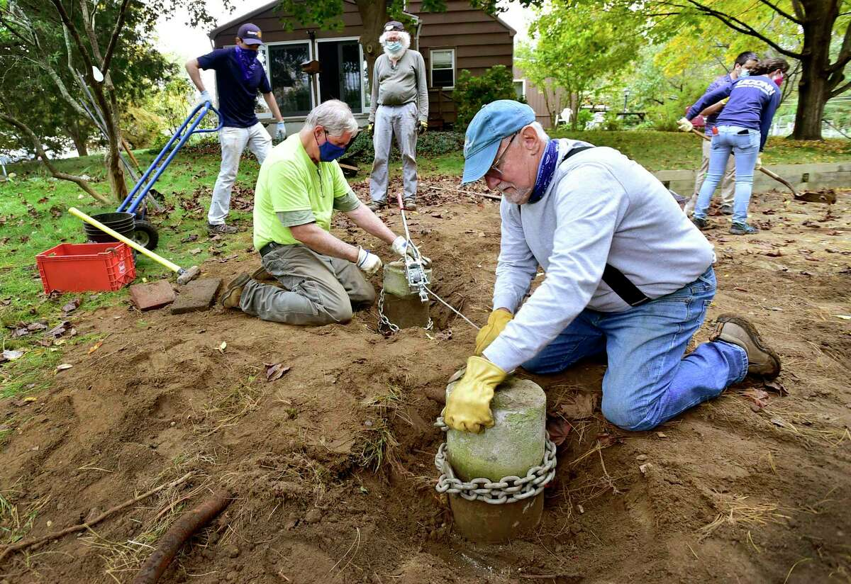 Steve Johnson, second from left, and Frank O'Hara, fourth from left, both of Milford, prepare to move concrete deck pilings as they volunteer with the Milford Land Conservation Trust.