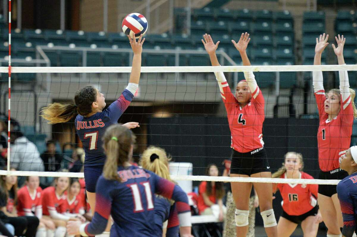 Renata Bolado Corona (7) of Dulles hits a shot as Perris Key (4) of Katy attempts a block during the third set of a Class 6A Region III bi-district volleyball playoff match between the Dulles Vikings and the Katy Tigers on Monday, November 4, 2019 at the Leonard Merrell Center, Katy, TX.