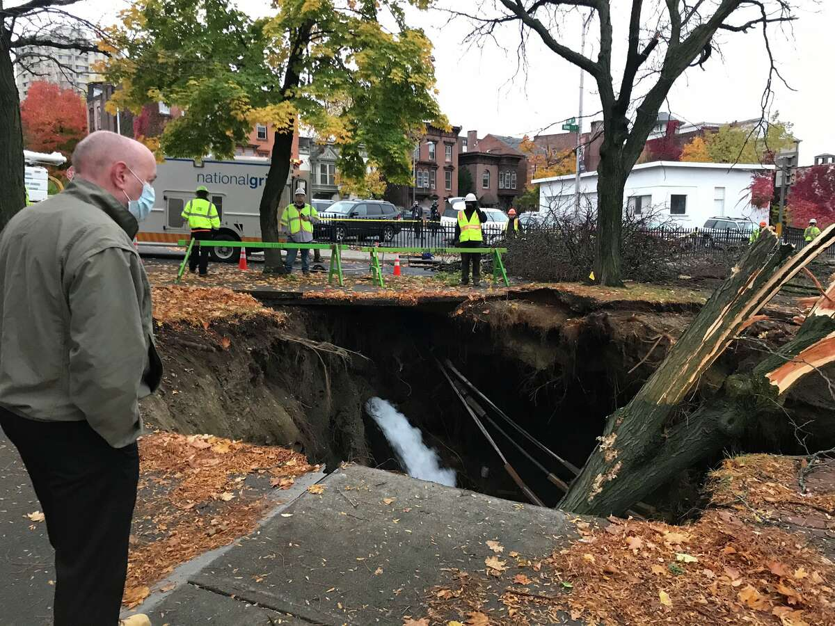 Mayor Patrick Madden surveys a sinkhole created by a water main break on Monday, Oct. 26.