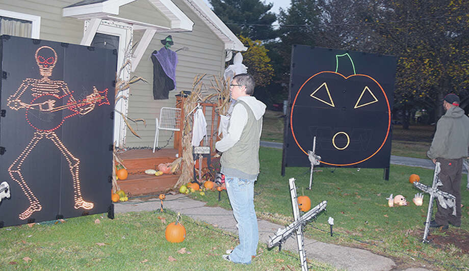 Rochelle Garner (center) and Drew Riley watch a light show they put together in front of their house in White Hall. Riley said he hopes the show can become a Halloween tradition. Photo: Marco Cartolano | Journal-Courier