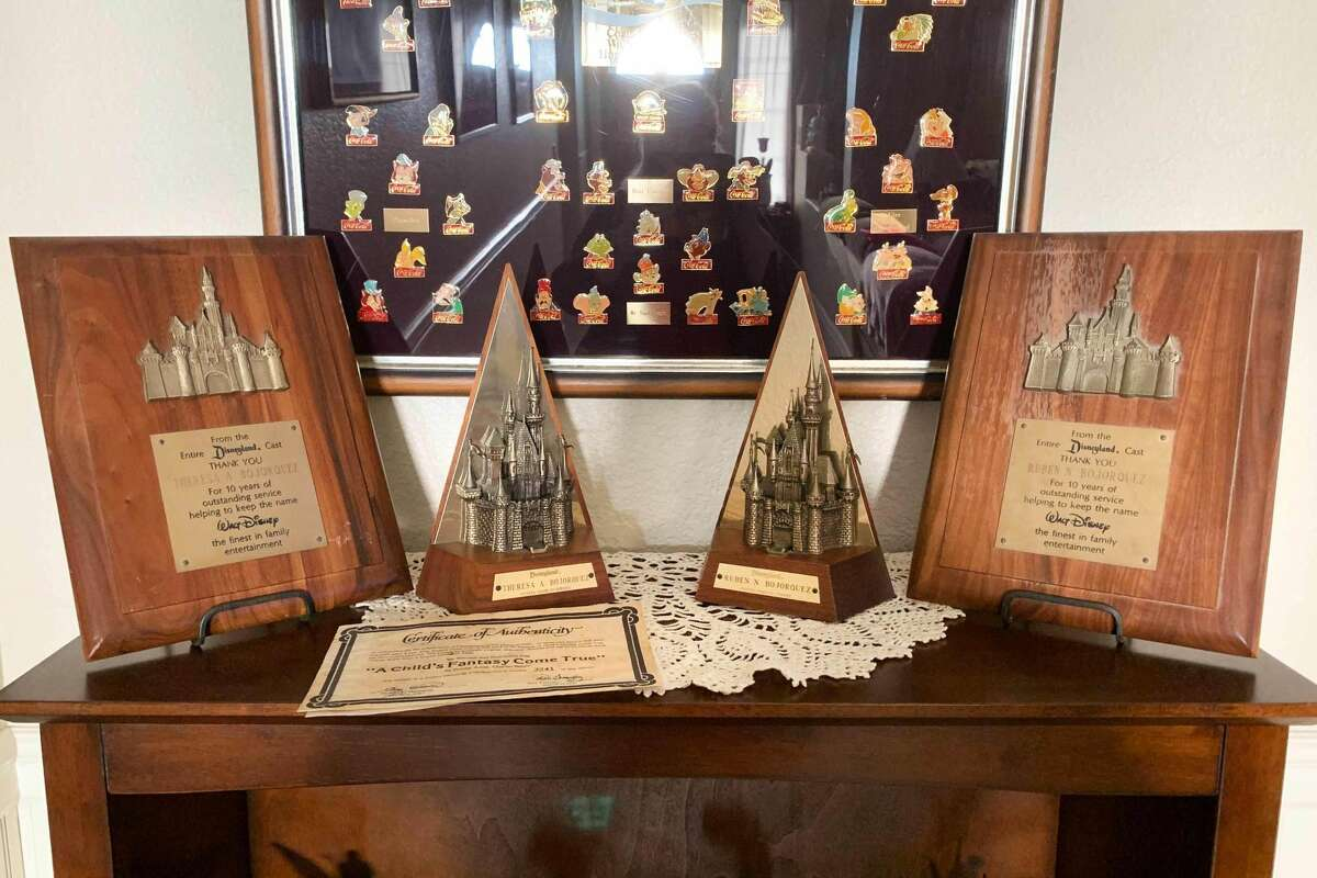 The bookshelf holding Theresa and Ruben's years of service awards from Disneyland.