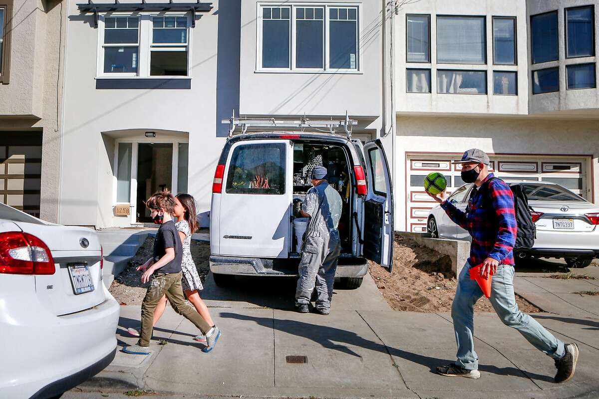 Cameron Adler (right), Leo, 7, and Abigail, 7, walk past Sonny Yang as he pulls materials from a work van outside of a single family home that's being renovated for sale in the Outer Sunset on Monday, October 26, 2020 in San Francisco, Calif.