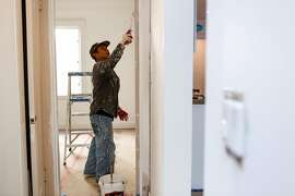 Yin Yang paints the interior of a single family home being renovated for sale in the Outer Sunset on Monday, October 26, 2020 in San Francisco, Calif.