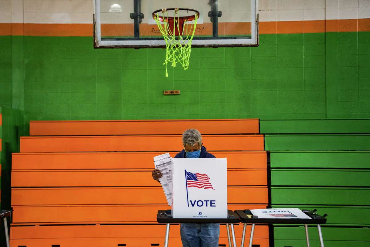 A voter casts a ballot at a polling station inside Frederick Douglass Academy during Michigan Primary in Detroit, Michigan on Aug. 4, 2020.