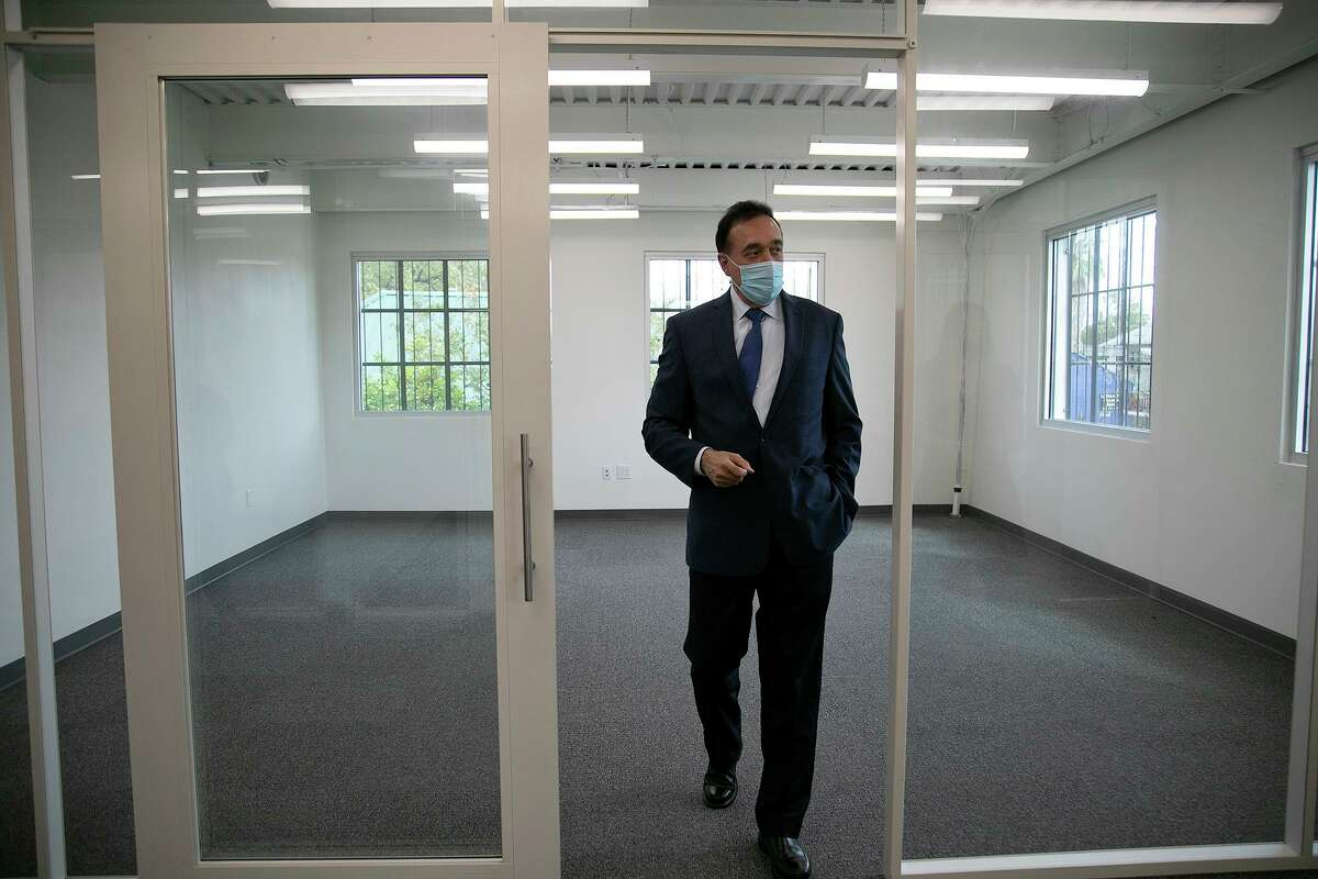 Henry Cisneros walks around a building that once housed his grandfather's print shop. He has been renovating it.