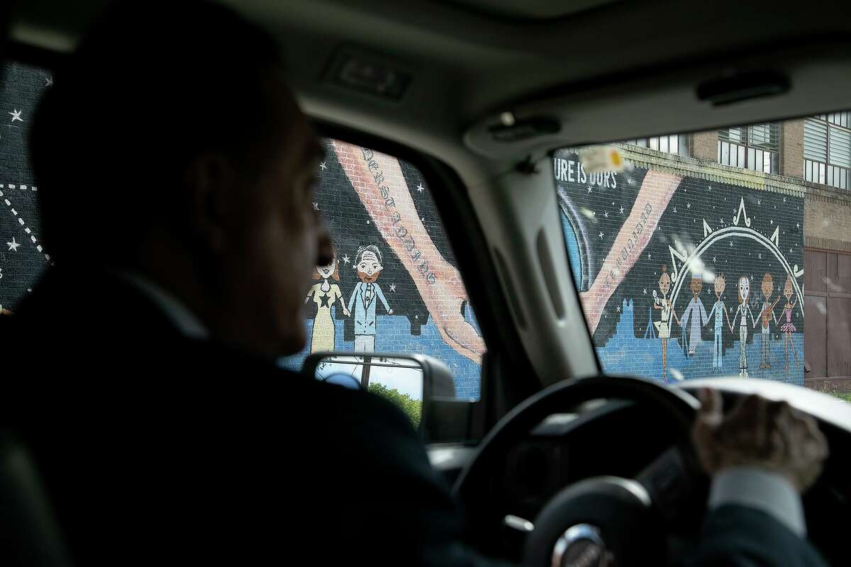 Henry Cisneros, reflected in the window of his vehicle, drives around the West Side where he grew up and still lives on Wednesday, Oct. 21, 2020.