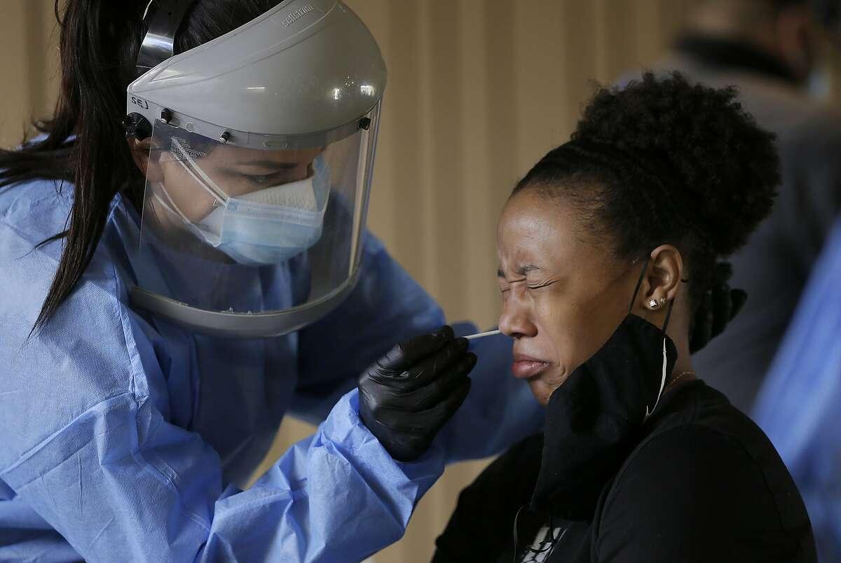 Sasha Jacquez tests he University of Texas at El Paso student Ariona Gill for the coronavirus.