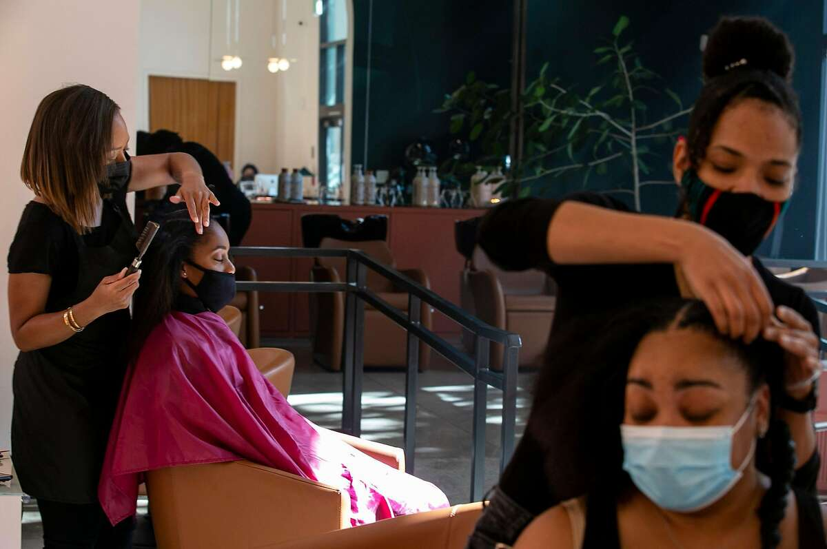 Stylist Jamilah Scott of Oakland styles client Crystal Obazuaye's hair during her appointment at GoodBody on Friday, Oct. 23, 2020 in Oakland, Calif.