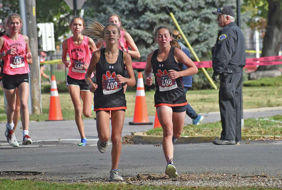 Edwardsville's Whitney Dyckman, left, and Olivia Coll cross the road during the Class 3A Granite City Regional. Photo: Matt Kamp|The Intelligencer