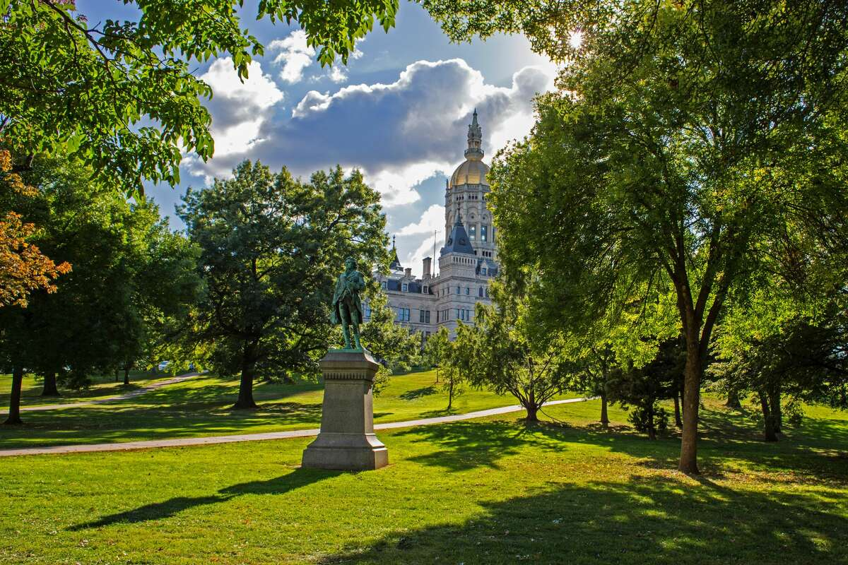 An artistic shot into the sun showing historic Capitol building located in downtown Hartford, CT. View is taken from Bushnell Park.