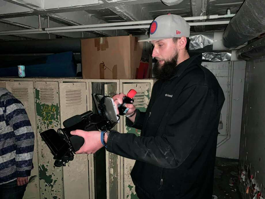 Tyler Kubacki leads one of the investigation teams through Port Austin's historic gymnasium investigating paranormal activity that reportedly has taken place there. (Courtesy Photo)