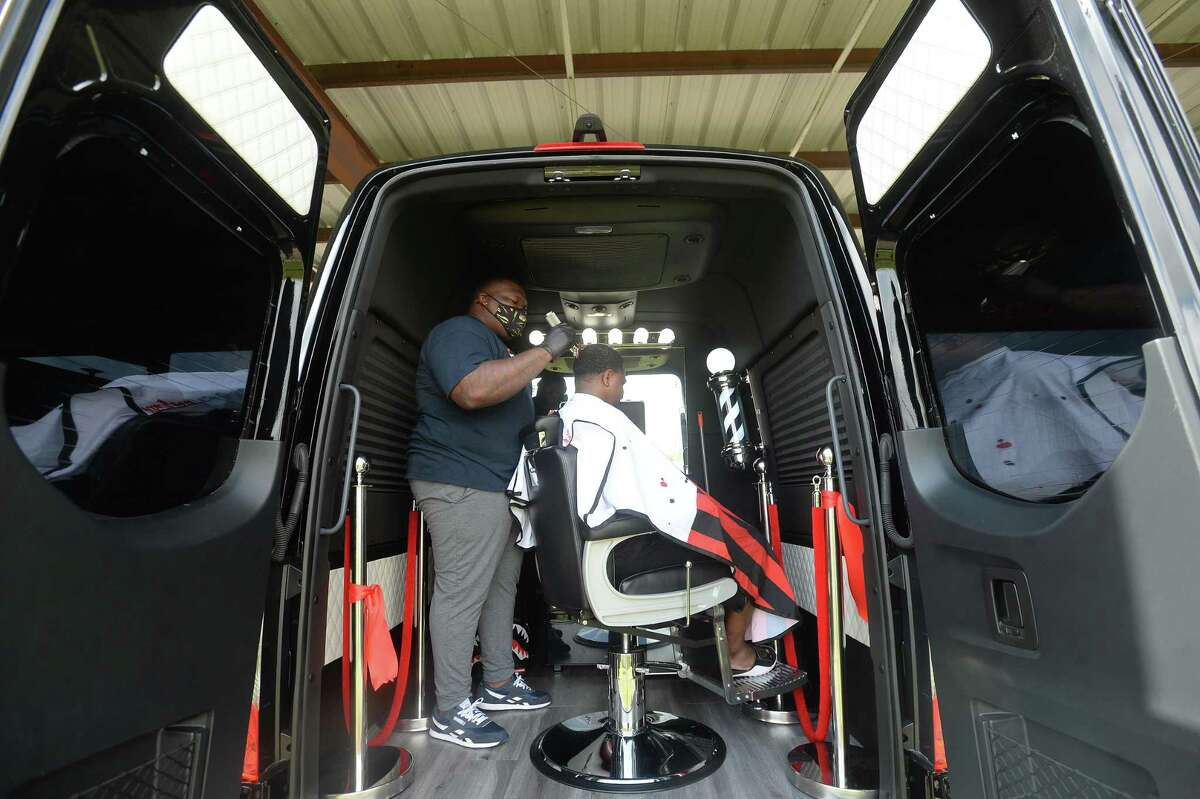 Ryan Tezeno gives a cut to Kendrick Miller inside his mobile barbershop Marathon Kutz. Tezeno launched the business Saturday, October 17, and has gotten numerous calls and requests since. Photo taken Thursday, October 22, 2020 Kim Brent/The Enterprise