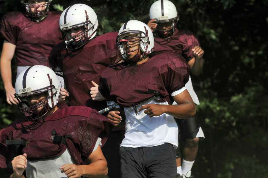 High school football -- Lansingburgh senior Marcus Little, foreground right, runs hills while doing conditioning drills with teammates at practice at the school in Troy.  ( Philip Kamrass / Times Union ) Photo: Philip Kamrass