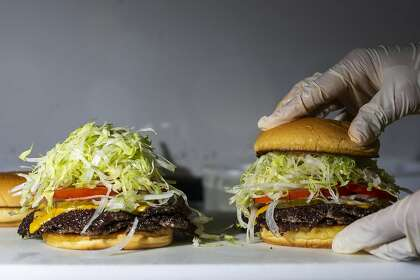 Amy Han tops a pair of OG Burgers during a Smish Smash pop-up event at Neptune's in Alameda.