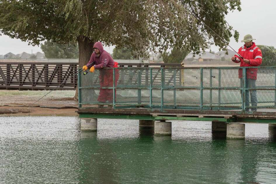 Americo De Ochoa, left and Santino Martinez decided to go fishing 10/27/2020 at CJ Kelly Park after being sent home from work early because of the weather. The pair had the pond to themselves as temperatures hovered at or below freezing. Tim Fischer/Reporter-Telegram