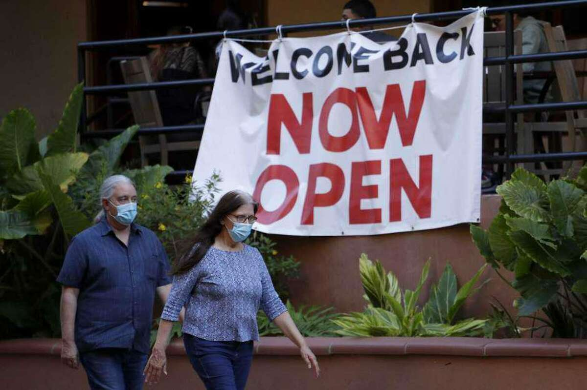 Visitors to the River Walk pass a restaurant that has reopened in San Antonio.