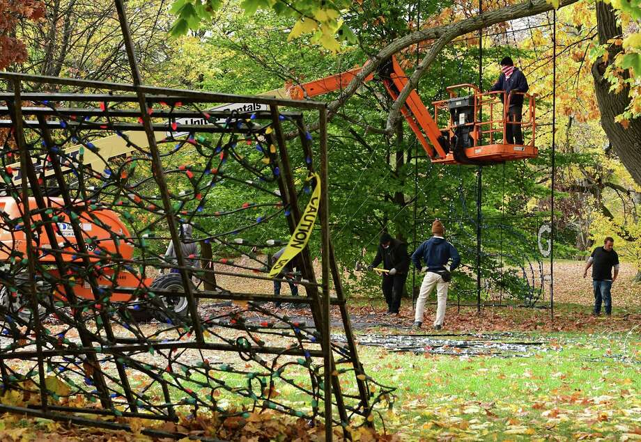 Workers, mostly from the Albany Police Athletic League (PAL), set up the God Bless the USA light display which is part of the Capital Holiday Lights in the Park on Tuesday, Oct. 27, 2020 in Albany, N.Y.  (Lori Van Buren/Times Union) Photo: Lori Van Buren, Albany Times Union