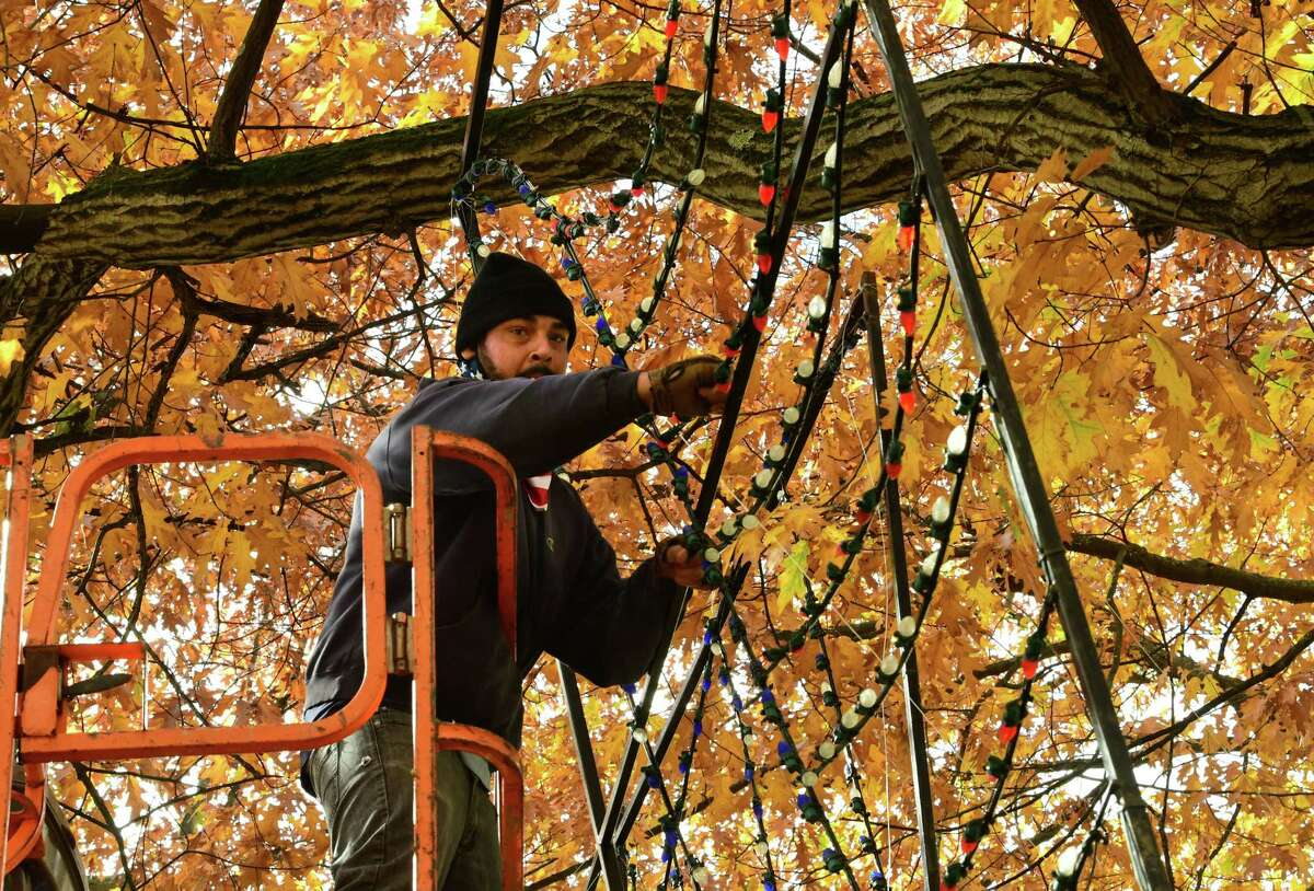 Albany Police Athletic League (PAL) worker Tomar Fantroy of Albany is seen on a lift setting up the God Bless the USA light display which is part of the Capital Holiday Lights in the Park on Tuesday, Oct. 27, 2020 in Albany, N.Y. (Lori Van Buren/Times Union)