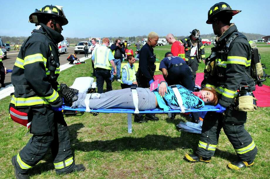 Jaime Aaron (center), 16, is carried to a triage area with fake injures by New Haven firefighters at Tweed New Haven Regional Airport during the airport's triennial disaster drill on 4/26/2011. Photo: Hearst Connecticut Media File