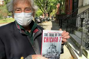 "George McNamee, 74, of Albany, holds a 50th-anniversary edition and movie tie-in paperback, ""The Trial of the Chicago 7,"" which he and three co-editors first published in 1970 as ""The Tails of Hoffman."" McNamee was an anti-Vietnam War demonstrator in the late-1960s and co-editor of the 1970 book on the trial of anti-war protesters at the 1968 Democratic National Convention in Chicago. It has been republished in a 50th-anniversary edition to coincide with the Aaron Sorkin movie, ""The Trial of the Chicago 7,"" now streaming on Netflix. (Paul Grondahl / Times Union)   (Paul Grondahl / Times Union)"