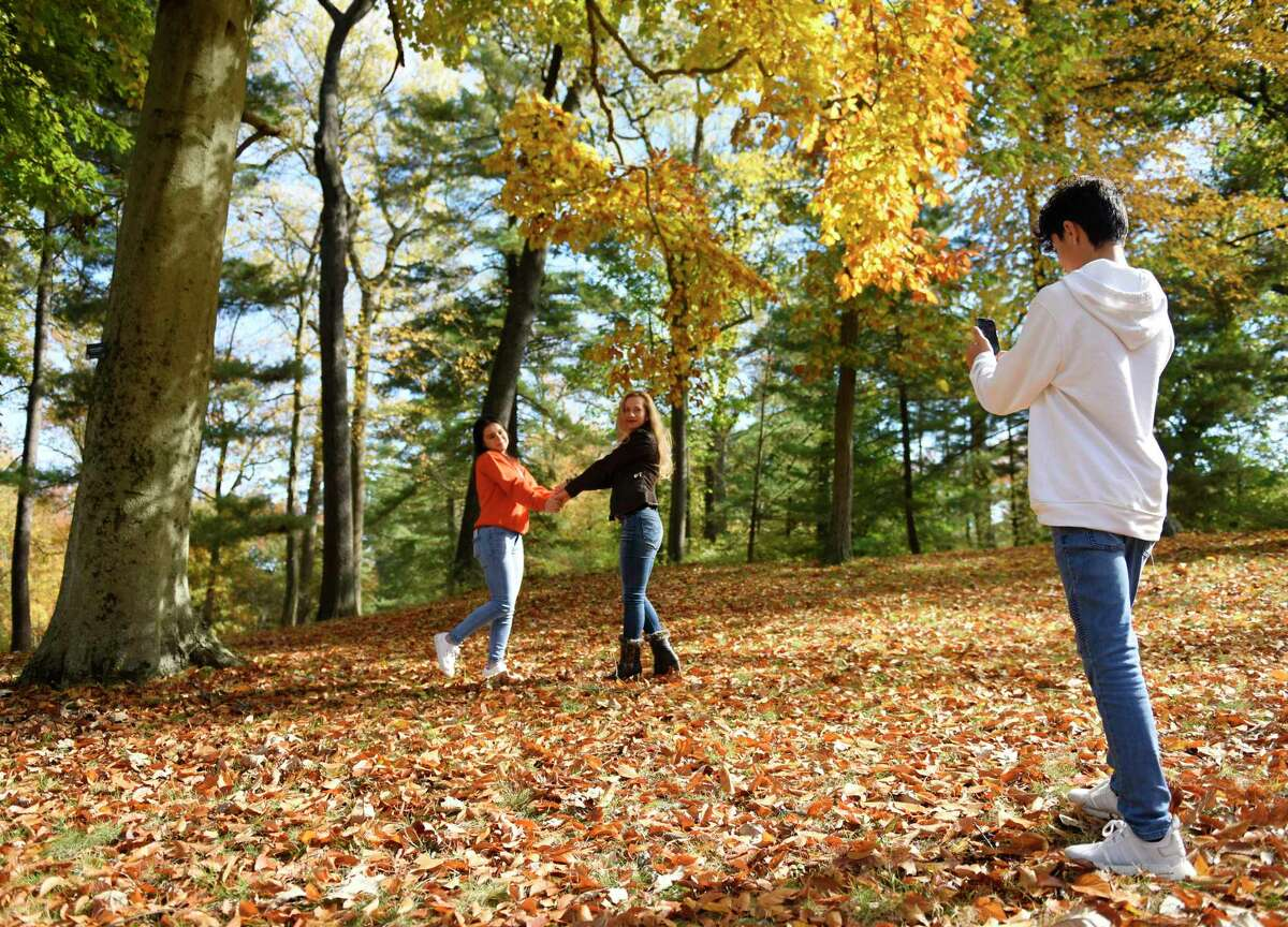 Stamford's Mildia Chinchilla, center, poses in the colorful fall foliage with her daughter, Katherine Chinchilla, 18, as her son, Jefferson Chinchilla, 13, takes a photo at Bruce Park in Greenwich, Conn. Tuesday, Oct. 27, 2020.